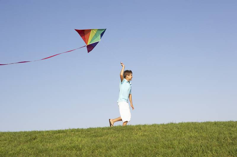 Young boy running with kite through field