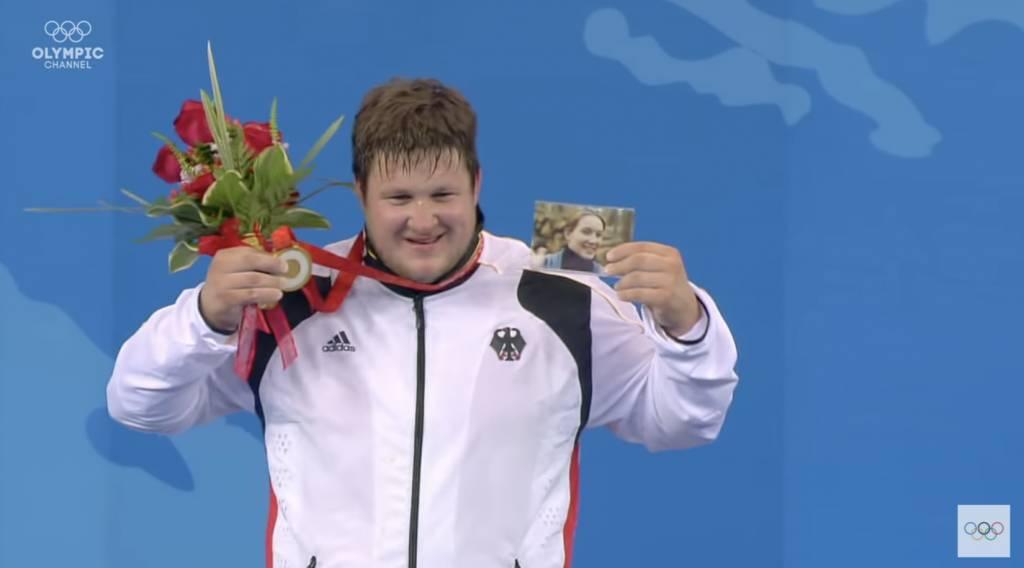施泰納終奪奧運金牌,頒獎台上舉起亡妻照片。(圖片來源:YouTube@Olympics)